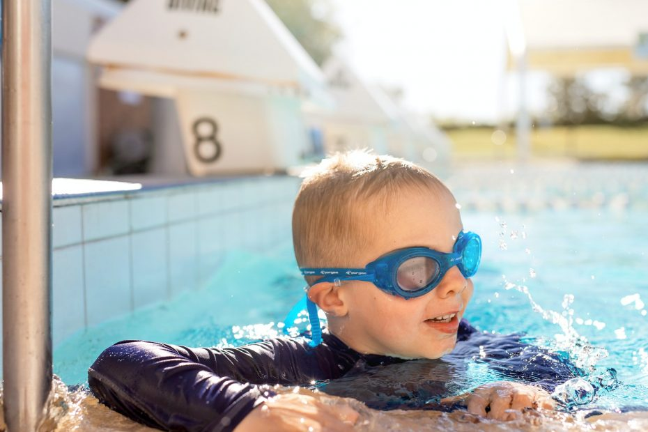 Child in goggles in swimming pool